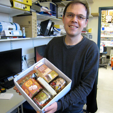 Christian Speck displays a box of German Christmas treats, a gift from of lab alumnus, Stefan Samel